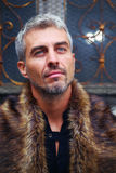Portrait of a sexy man in wolf  fur and ornamental medieval window on background Stock Photo