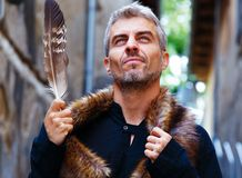 Portrait of a man and wolf furry and eagle feathers, a disgruntled expression on his face. Stock Image