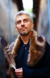 Portrait of a man and wolf furry and eagle feathers, and ornamental medieval window on background Stock Photos