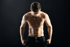 Portrait of a sexy muscular shirtless man on dark background Royalty Free Stock Images