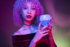 Portrait of a sexy and mysterious woman drinking an alcoholic dr. Portrait of a sexy and mysterious woman drinking a blue alcoholic drink Stock Image