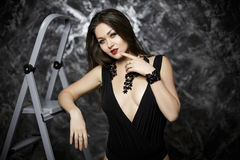 Portrait of sexy and seductive brunette woman with red lipstick in black bodysuit on dark background. Portrait of young sexy and seductive brunette woman with Stock Images