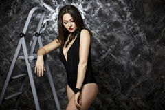 Portrait of sexy and seductive brunette woman with red lipstick in black bodysuit on dark background. Portrait of young sexy and seductive brunette woman with Stock Photo
