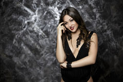 Portrait of sexy and seductive brunette woman with red lipstick in black bodysuit on dark background. Portrait of young sexy and seductive brunette woman with Stock Photography