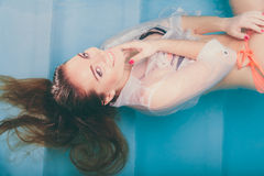 Portrait of sexy seductive woman in water. Portrait of sexy seductive woman floating in swimming pool water. Pretty alluring young girl wearing wet white shirt Royalty Free Stock Image