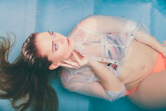 Portrait of sexy seductive woman in water. Portrait of sexy seductive woman floating in swimming pool water. Pretty alluring young girl wearing wet white shirt Royalty Free Stock Images