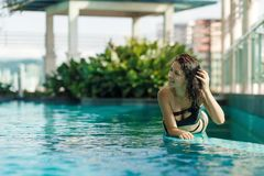 Portrait of a sexy smiling caucasian woman in a swimsuit lay on the edge of a rooftop pool with green bushes and city views. Asia royalty free stock photo