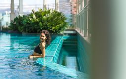 Portrait of a sexy smiling caucasian woman in a swimsuit relaxing in a rooftop pool with green bushes and city views. Asia weekend royalty free stock images
