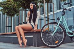 Portrait of a sexy hippie female wearing blouse and shorts in a headband, sits barefoot on a bench near city bike. Portrait of a sexy smiling hippie female Royalty Free Stock Photography