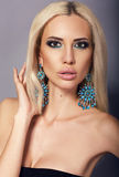 Portrait of sexy woman with blond hair with bright makeup. Fashion studio photo of sexy beautiful model with blond straight hair with bright makeup and bijou Royalty Free Stock Photos