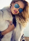 Portrait of sexy woman with blond hair in fur coat and sunglasse Royalty Free Stock Photography