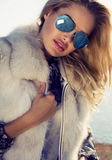 Portrait of sexy woman with blond hair in fur coat and sunglasses Royalty Free Stock Photo