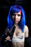 Portrait of sexy woman with blue hair holding gun and looking as killer Royalty Free Stock Image