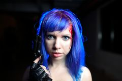 Portrait of sexy woman with blue hair holding gun and looking as killer Stock Photos