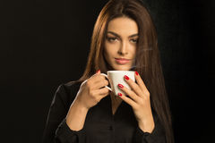 Portrait of sexy woman enjoying a hot cup of coffee on a dark ba Royalty Free Stock Photography