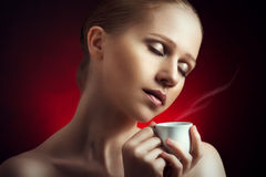 Sexy woman enjoying a hot cup of coffee on a dark background Royalty Free Stock Image