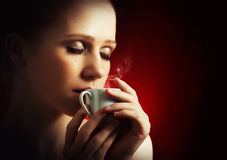 Sexy woman enjoying a hot cup of coffee on a dark background Stock Photos