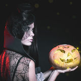 Portrait of sexy woman with gothic makeup smokey eyes. Holding a pumpkin. Vampire, evil. Goth. Horror. Secret. Fashion. Venetian carnival. Hot babe. Halloween Royalty Free Stock Photos