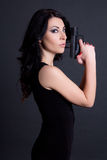 Portrait of woman secret agent posing with gun over grey Stock Photos
