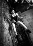 Portrait of sexy woman sitting on ground against brick wall Royalty Free Stock Photography