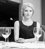 Portrait of sexy woman sitting at restaurant behind table Stock Photos