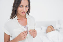 Portrait of a sexy woman sneaking out of bed. Portrait of a sexy women sneaking out of bed next to an asleep man Stock Image