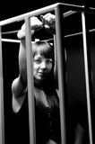 Portrait of sexy woman wearing handcuffs in cage Stock Photo