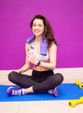 Portrait of a sexy woman after a workout with a towel over her shoulder holding a bottle of water Stock Images