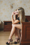 Portrait of sexy young blonde woman in lingerie sitting on the floor near the bed Stock Images