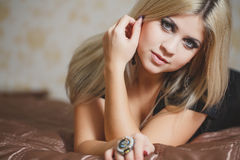 Portrait of sexy young blonde woman in lingerie sitting on the floor near the bed Stock Photography