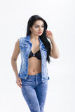 Portrait of sexy young brunette woman with long hair in denim vest on white background. Royalty Free Stock Photography
