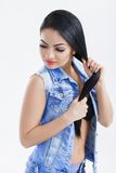 Portrait of sexy young brunette woman with long hair in denim vest on white background. Royalty Free Stock Photo