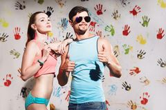 Portrait of sexy young couple with thumbs up sign on a funny pos. Happy smiling couple in beach clothes on funny background Stock Photo