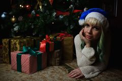 Portrait of young girl under Christmas tree with presents Stock Photo
