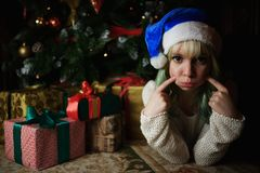 Portrait of sexy young girl under Christmas tree with presents Royalty Free Stock Image