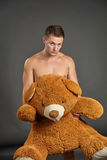 Portrait of a sexy young man with big plush bear. Against grey background Royalty Free Stock Image