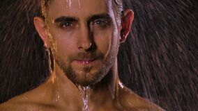 Portrait of a sexy young man under shower jets who looks erotically into the camera. Water flows down his face creating