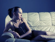 Portrait of sexy young model on sofa Stock Images