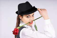 Portrait of a sexy young woman. Portrait of a beautiful young woman wearing white blouse, black pinstriped gilet and black hat. The woman is holding a red rose Stock Images