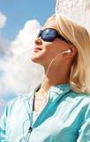 Portrait of sexy young woman listening music. Portrait of young blond woman listening music, wire on the wind Royalty Free Stock Image
