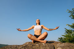 Portrait of sexy young woman with muscular body in sporrtswear practicing yoga on the cliff. Blue sky background Stock Image