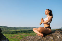 Portrait of sexy young woman in sporrtswear practicing yoga on the cliff. Green mountain landscape background Stock Image