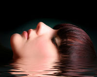 Portrait of a young woman in water. Portrait of a young woman on black in water royalty free stock images