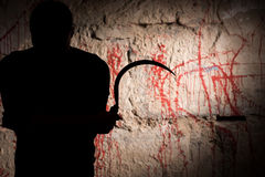 Portrait of shadowy figure holding blade near blood stained wall. For concept about murder and scary Halloween holiday Royalty Free Stock Photography