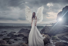 Portrait of the shining angel on the sharp rock Royalty Free Stock Photos
