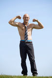 Portrait of shirtless bald young man wearing tie holds his arms Royalty Free Stock Photo