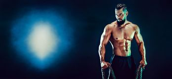 Portrait of shirtless bodybuilder. Muscular man posing in studio. Muscular bearded bodybuilder man Posing with rope in studio stock photos
