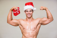 Portrait of shirtless macho man in santa hat holding gift Stock Photography