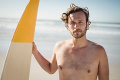Portrait of shirtless man holding surfboard at beach Stock Images