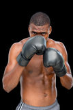 Portrait of a shirtless muscular boxer in defensive stance. Over black background Stock Photos
